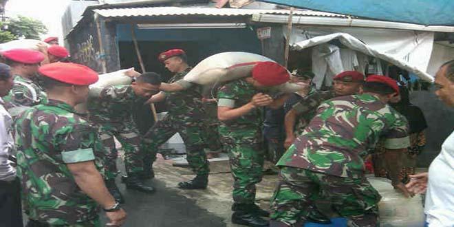 Prajurit Kopassus mengangkut karung beras utk pengungsi lenteng Agung