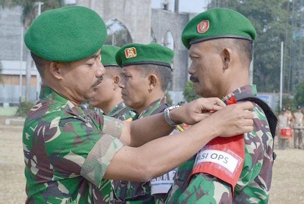 Kasrem 081 DSJ sedang menyematkan tanda peserta latihan