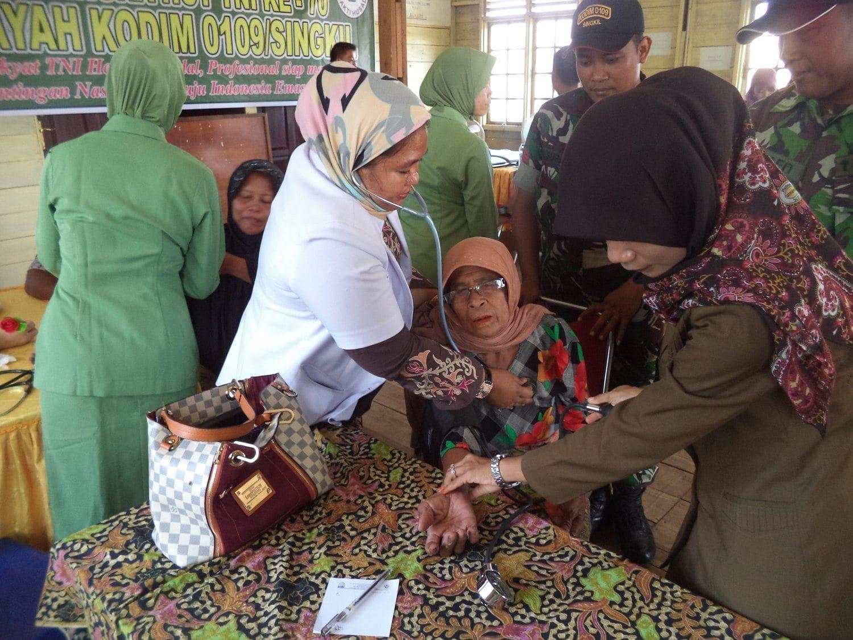Prajurit Kodim 0109/Singkil Memapah Masyarakat Yang Akan Ikut Pengobatan Massal