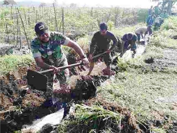 Anggota Koramil Wates bersama masyarakat perbaikan saluran irigasi non permanen