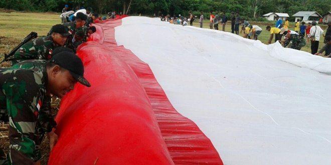 Satgas Pamtas RI-PNG Yonif Mekanis 411/Pandawa Kostrad dan KNPI Kab. Keerom Bentangkan Bendera Merah Putih Raksasa