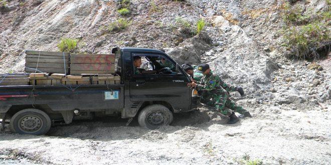 Prajurit TNI Bantu Kendaraan Warga Poso Yang Terperosok Lumpur