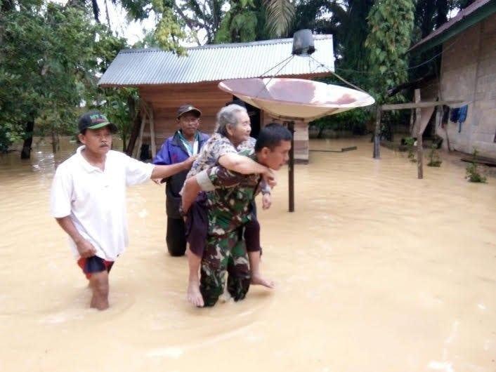 Prajurit TNI Gendong Wanita Lansia Menembus Banjir