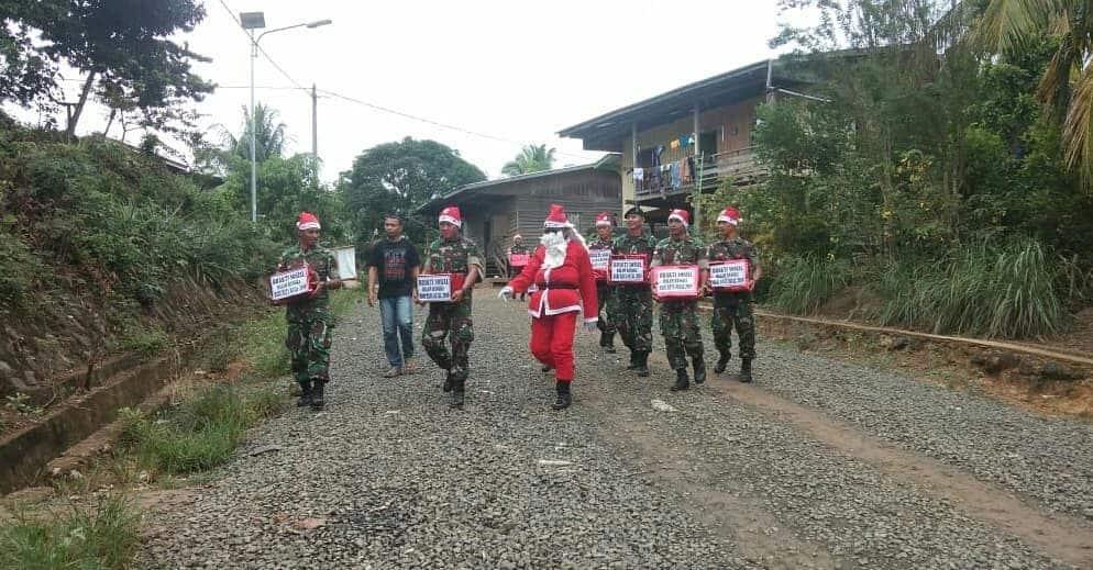 Keliling Kampung, Sinterklas Satgas Yonif R 600 Bagi Kado Natal