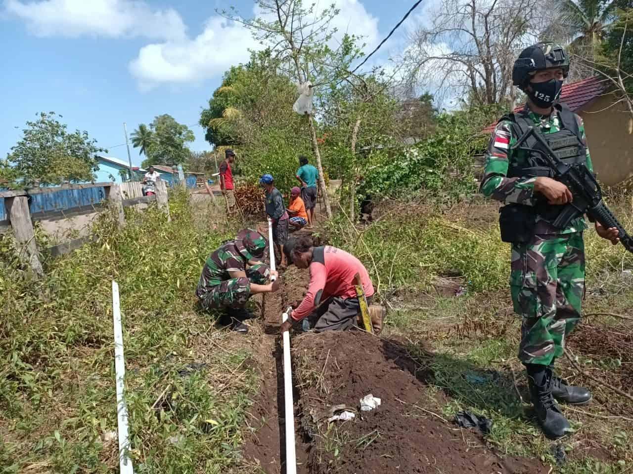 Prajurit Satgas Pamtas Yonif 125/Si'mbisa Berama Warga Kampung Kuler Pasang Pipa Saluran Air Bersih