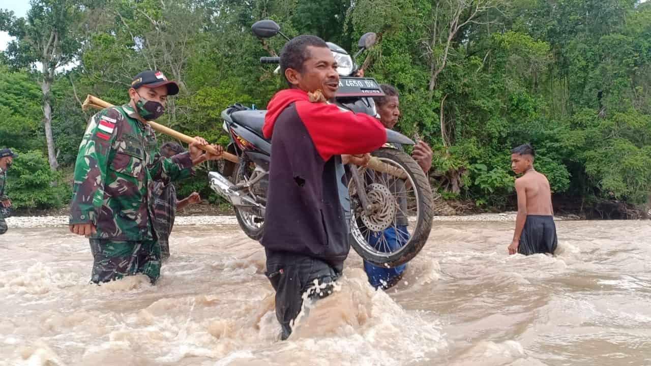 Satgas Yonarmed 3/105 Tarik Bantu Warga Lewati Luapan Air Sungai Boen
