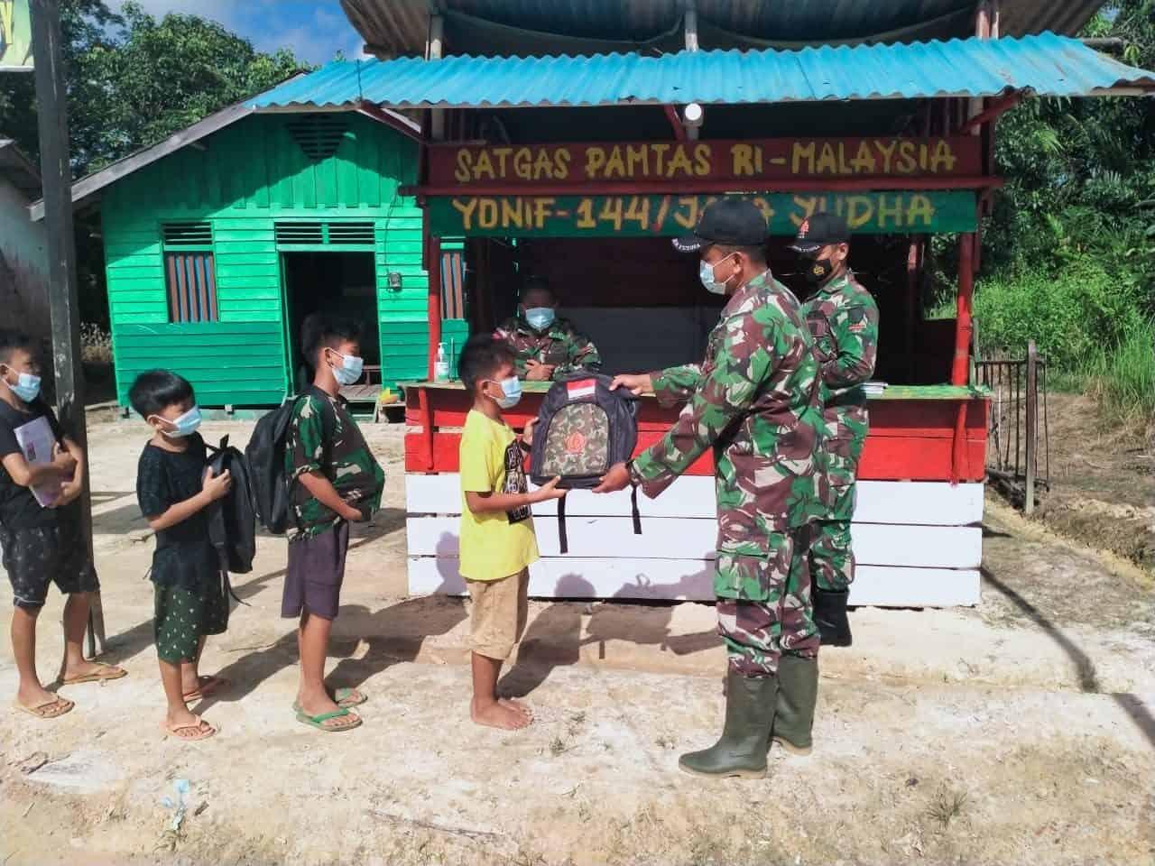 Personel Satgas Yonif 144/JY Berikan Bantuan Tas Sekolah