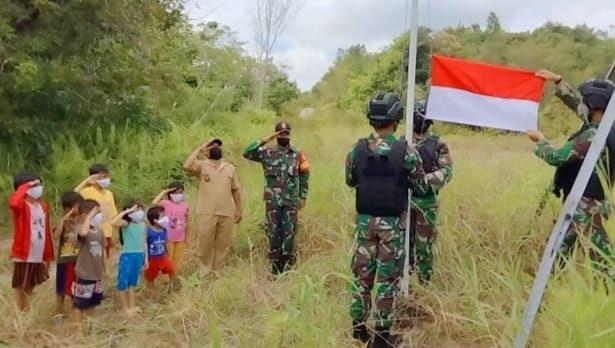 Sambut HUT RI, Satgas Yonif 144/JY Bersama Warga Pasang Bendera di Depan Rumah Panjang