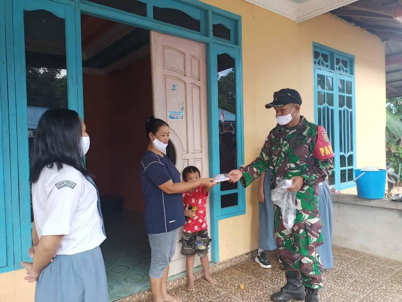 Personel Satgas Yonif 144/JY Sosialisasikan Prokes dan Bagikan Masker Warga di Perbatasan