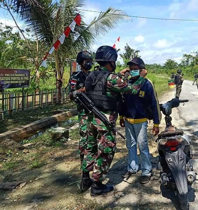 Satgas Yonif 512/QY Bagikan Masker Pada Masyarakat Yang Melintas Di depan Pos Perbatasan