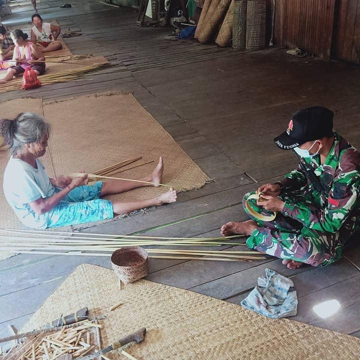 Lestarikan Tradisi, Personel Satgas Yonif 144/JY Bantu Warga Buat Anyaman Tikar