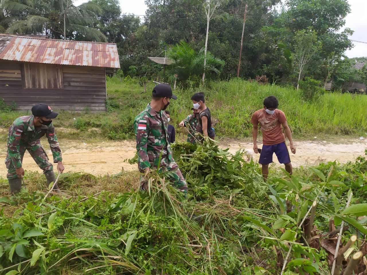 Pelihara Nilai Gotong Royong, Satgas Yonif 144/JY Bersama Warga Bersihkan Jalan Desa