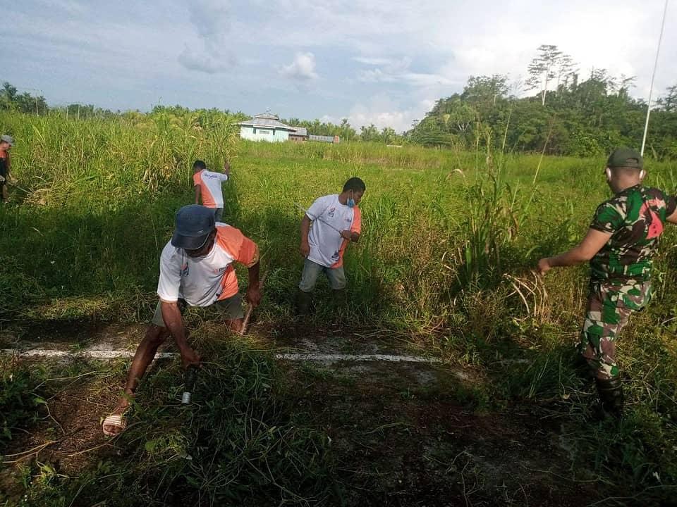 Satgas Yonif 131 Bersama Warga Gotong Royong Bersihkan Lapangan Kampung Pitewi