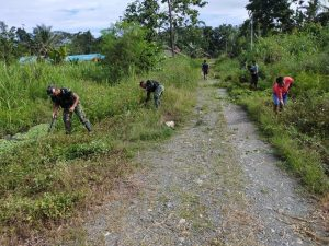 Satgas Yonmek 403 Bersama Warga Bersihkan Jalan Masuk SMP di Kampung Bompay