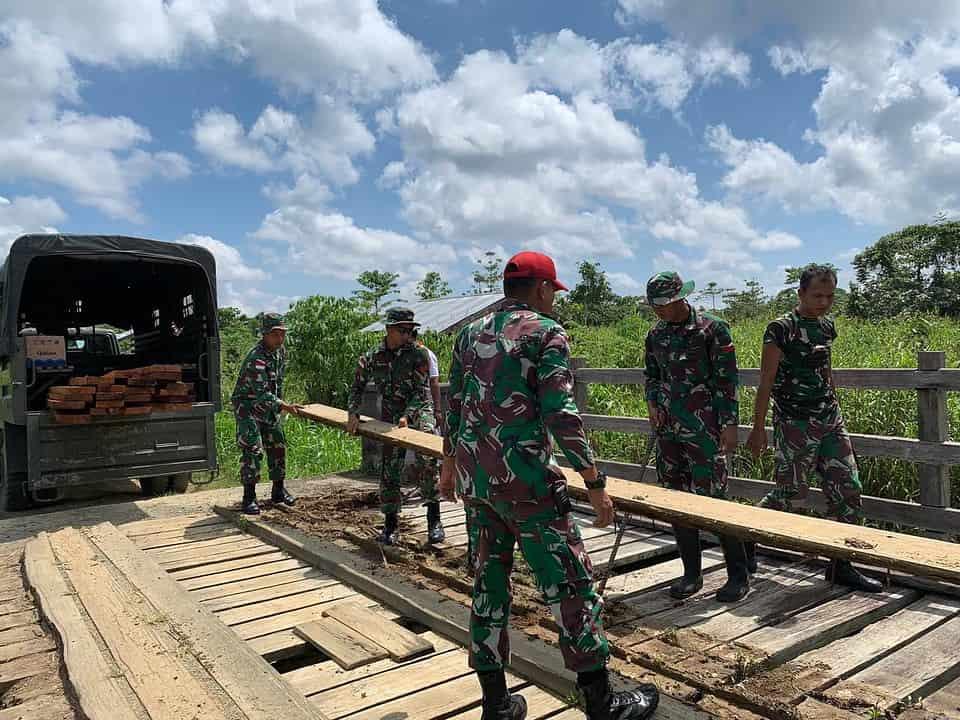Rusak dan Berlubang, Satgas Yonmek 403 Bersama Masyarakat Gotong Royong Perbaiki Jembatan Kayu di Papua